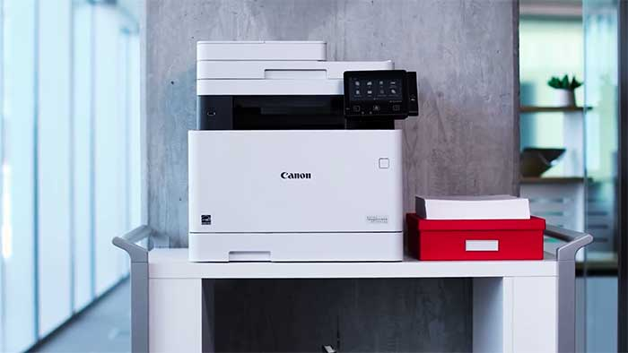Canon printer next to a stack of invoices