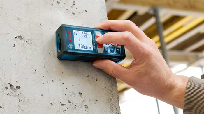 Bosch laser tool checking the distance between two walls