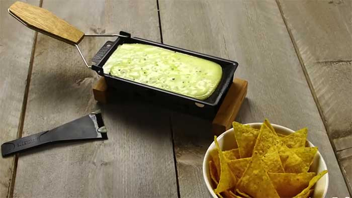Boska Holland partyclette with melted cheese and a bowl of nachos