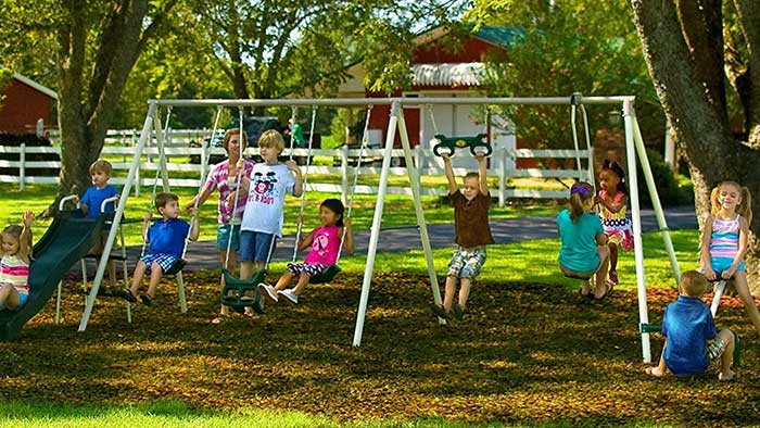 Children playing on an outdoor swing and playset