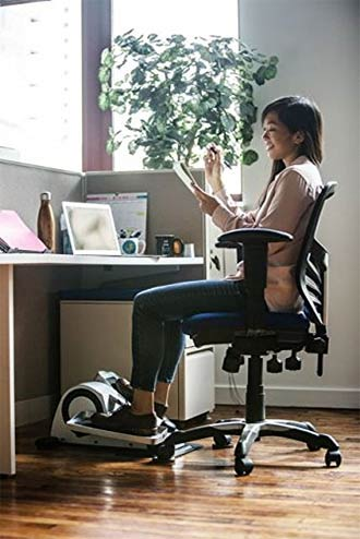 Woman sitting at her desk while peddling on a small elliptical bicycle