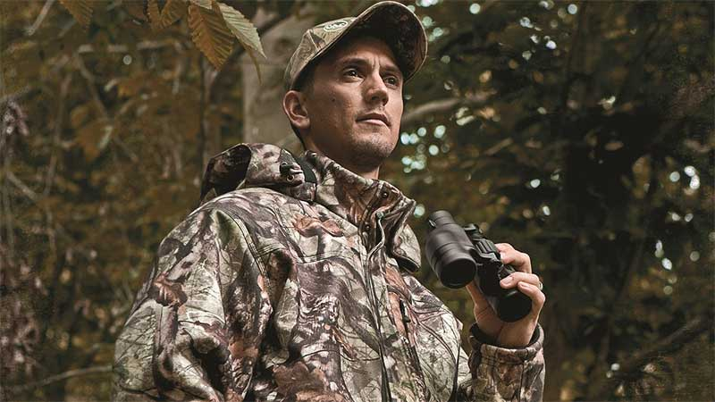 Man wearing a dewalt camo heated coat for hunting