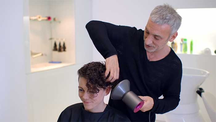 Hairdresser blowing air using a dyson hair dryer with a diffuser attached