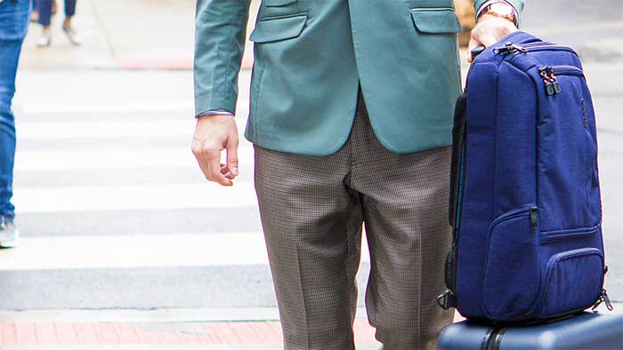 blue backpack next to a man in a suit