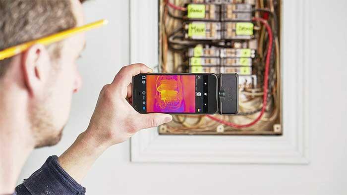 Man detecting thermal gradients with a FLIR camera
