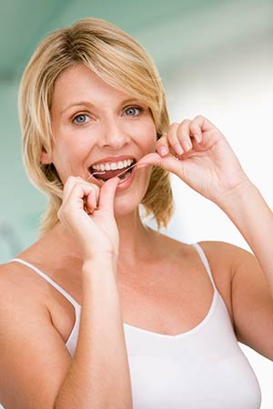 Woman flossing with a piece of string