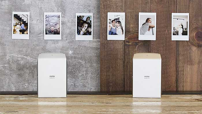 Fujifilm Instax share sp2 portable printer next to some photos hanged on a wall