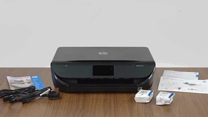 Hp envy 5055 printer on a wooden desk