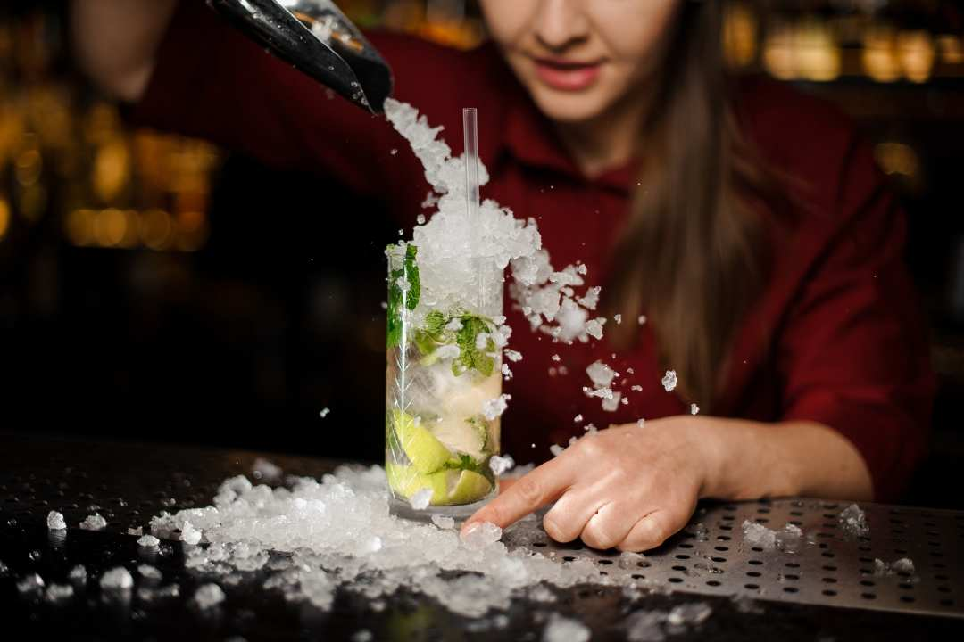 bartender pouring crushed ice on a mojito drink