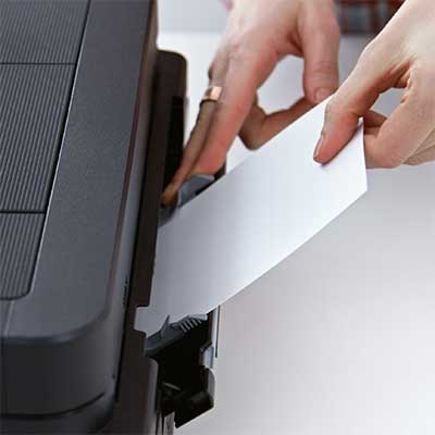 Hands inserting carstock paper into a printer's tray