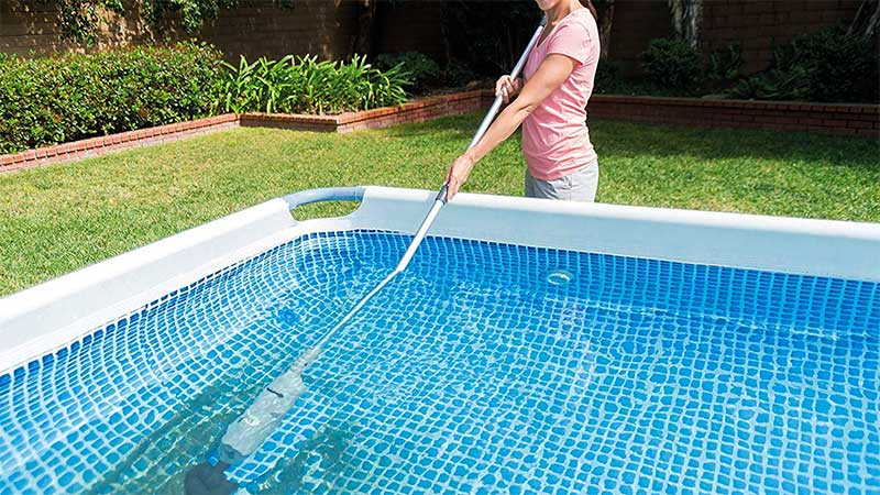 woman sweeping a swimming pool floor