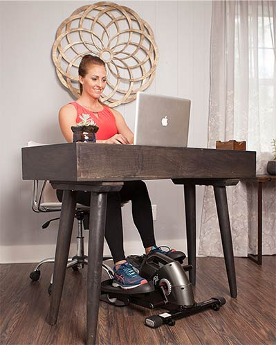 Woman working at her desk with a jfit elliptical trainer