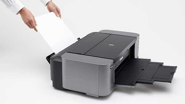 Man loading the canon pixma pro 100 paper tray with a thick cardstock paper sheet