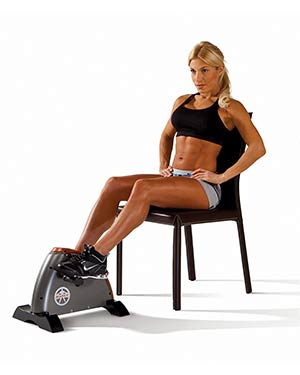 Woman using a marcy cardio mini bicycle while sitting on an office chair