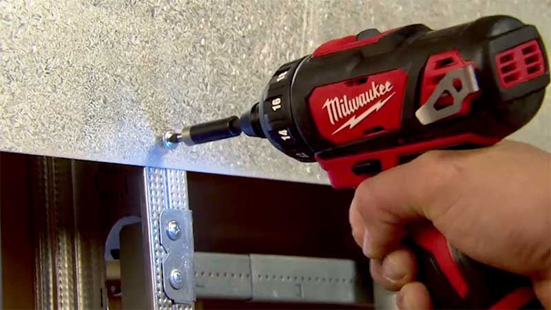 Milwaukee screwdriver removing a screw from a metal plate