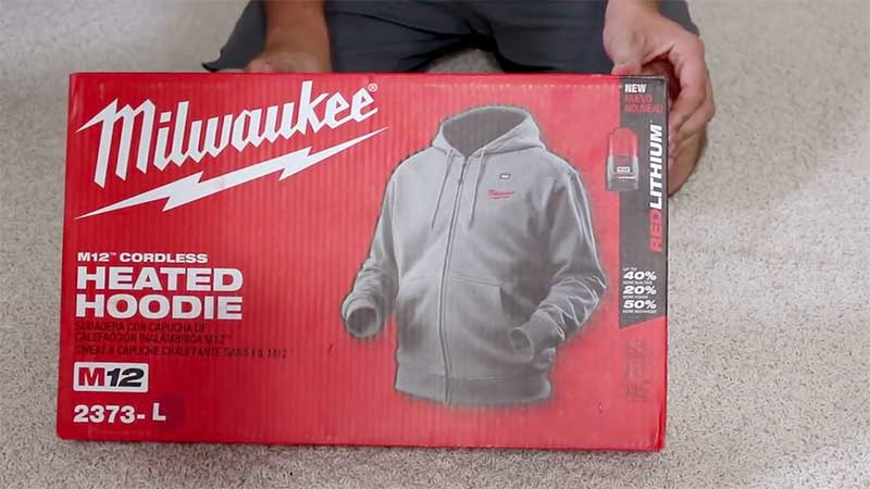 Man showing the milwaukee heated hoodie retail box