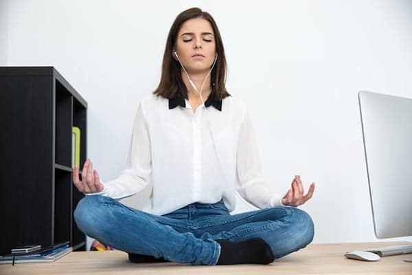 Woman meditating on an office desk