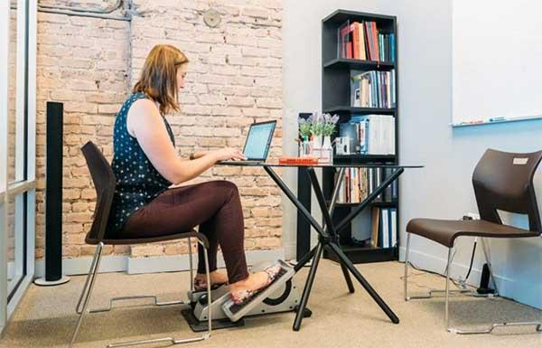 Woman peddling on a cubii elliptical trainer at her desk