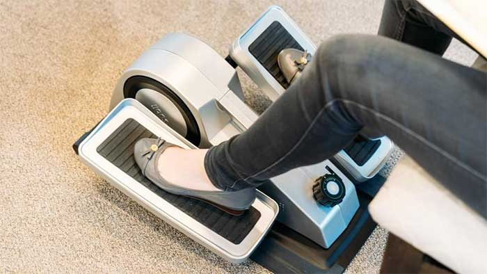 woman feet peddling on a desk exerciser