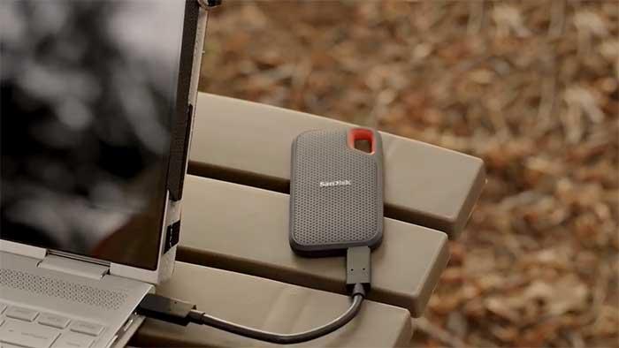 Portable disk next to a laptop on a wooden garden table