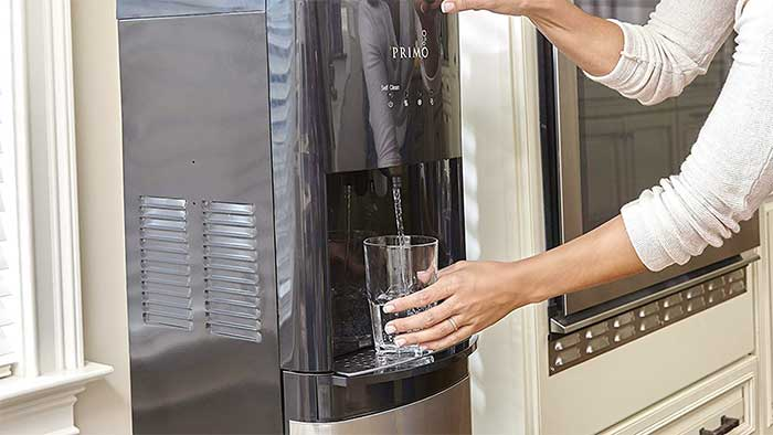 Woman pouring a glass of water at a dispenser