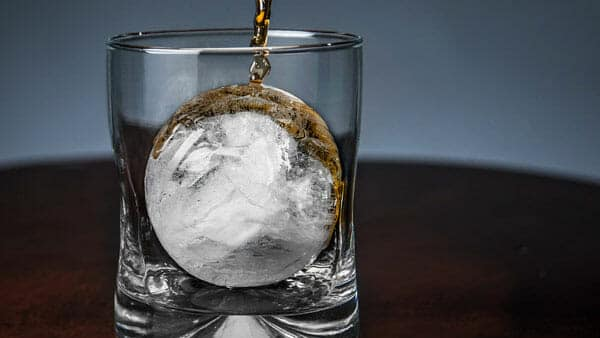 pouring alcohol on an ice sphere