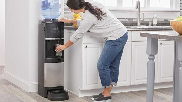 woman filling a cup at a water dispenser