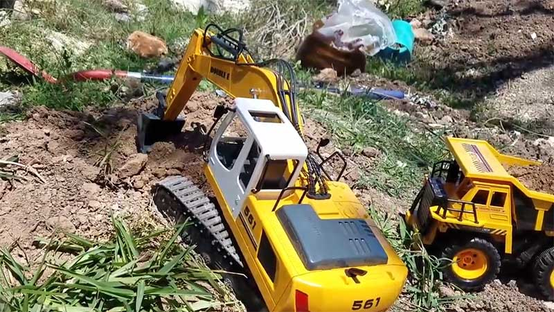 RC Excavator toy digging into soil