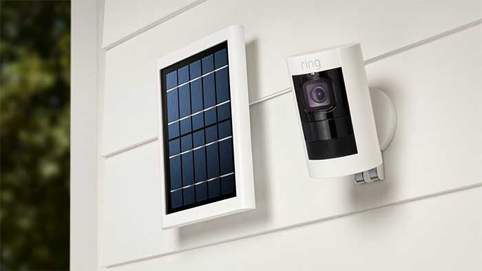 Ring stick up cam next to the solar panel, mounted on an outside wall of a house