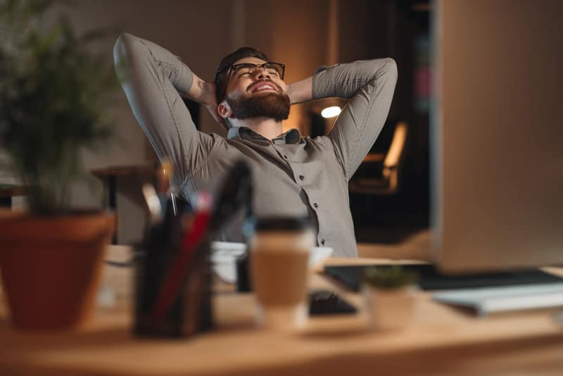 Bearded man stretching at his desk