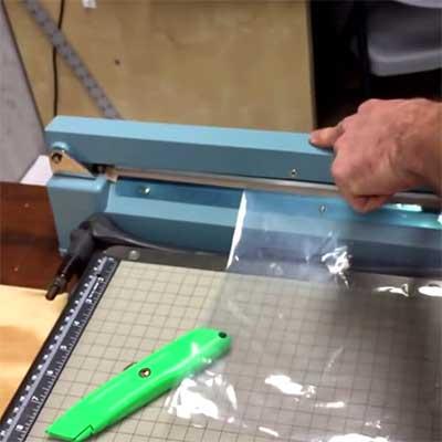 Man sealing a plastic bag using an impulse sealer