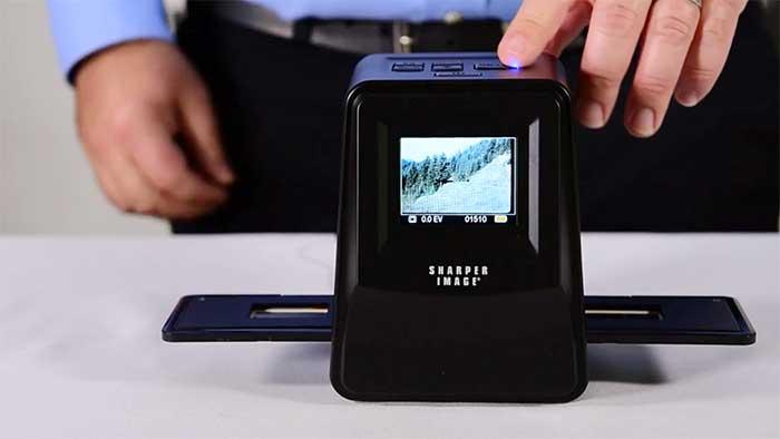 man scanning a photo negative with a sharper image scanner