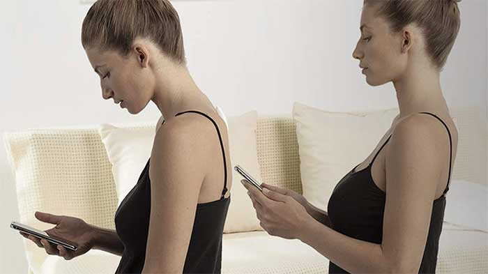 Woman getting a reminder for slouching on her smartphone then correcting her stand