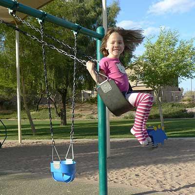 little girl using a steel swing