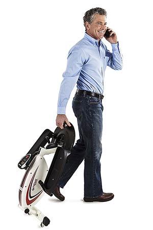 Business man transporting a mini desk elliptical bike