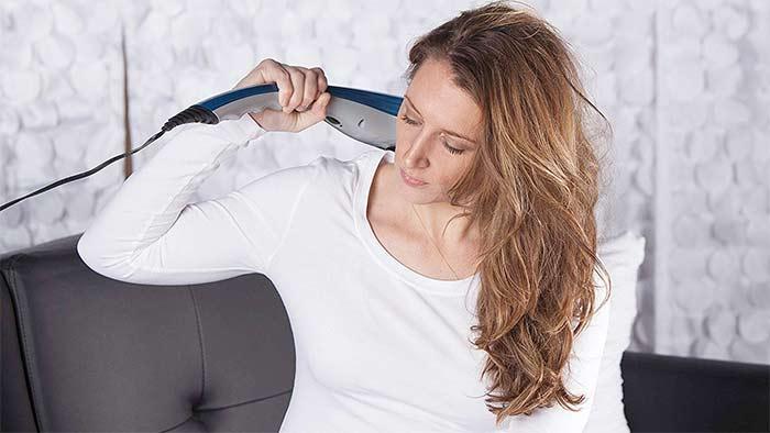 Woman using an handheld massage device