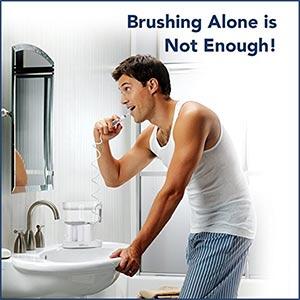 Man using a waterflosser in his bathroom