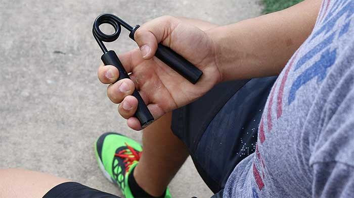 young man holding a metal hand gripper